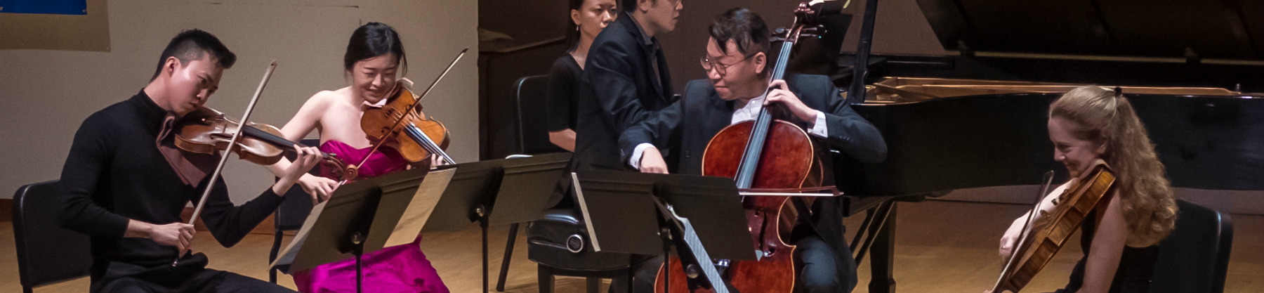 An orchestra with violins and a grand piano performs on stage.