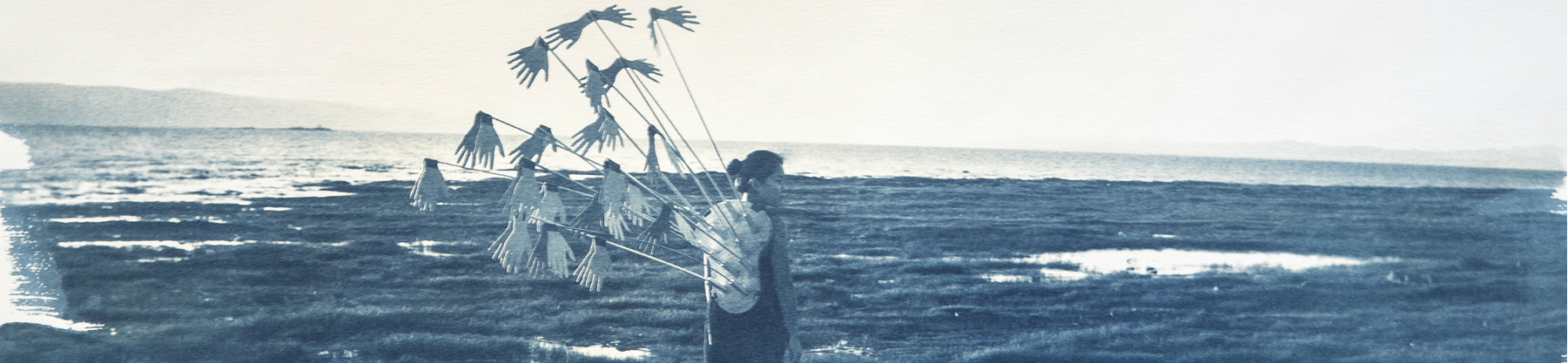 A cyanotype photo of a woman on a shoreline with an abstract art piece strapped to her back.