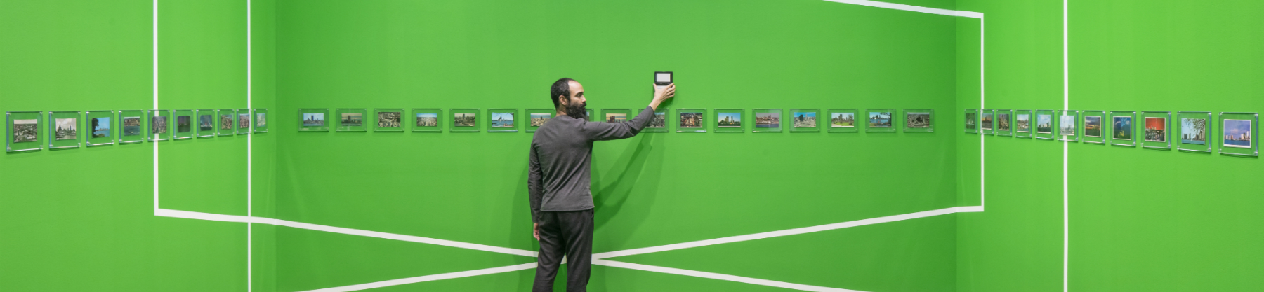 A man stands in the middle of a gallery of photographs. The walls are bright green and the photos are hung in a horizontal line around the room.