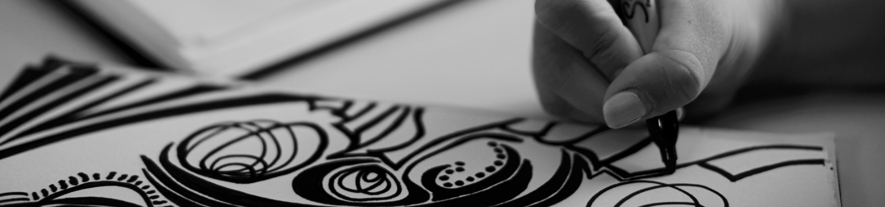 A hand is drawing a design on paper with a black sharpie marker.