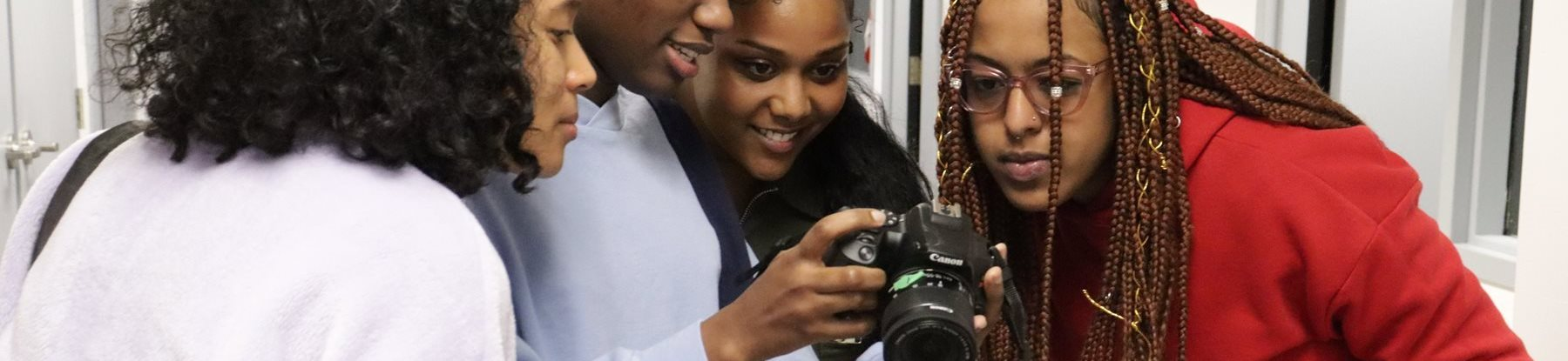 A group of students look into the viewfinder of a digital camera