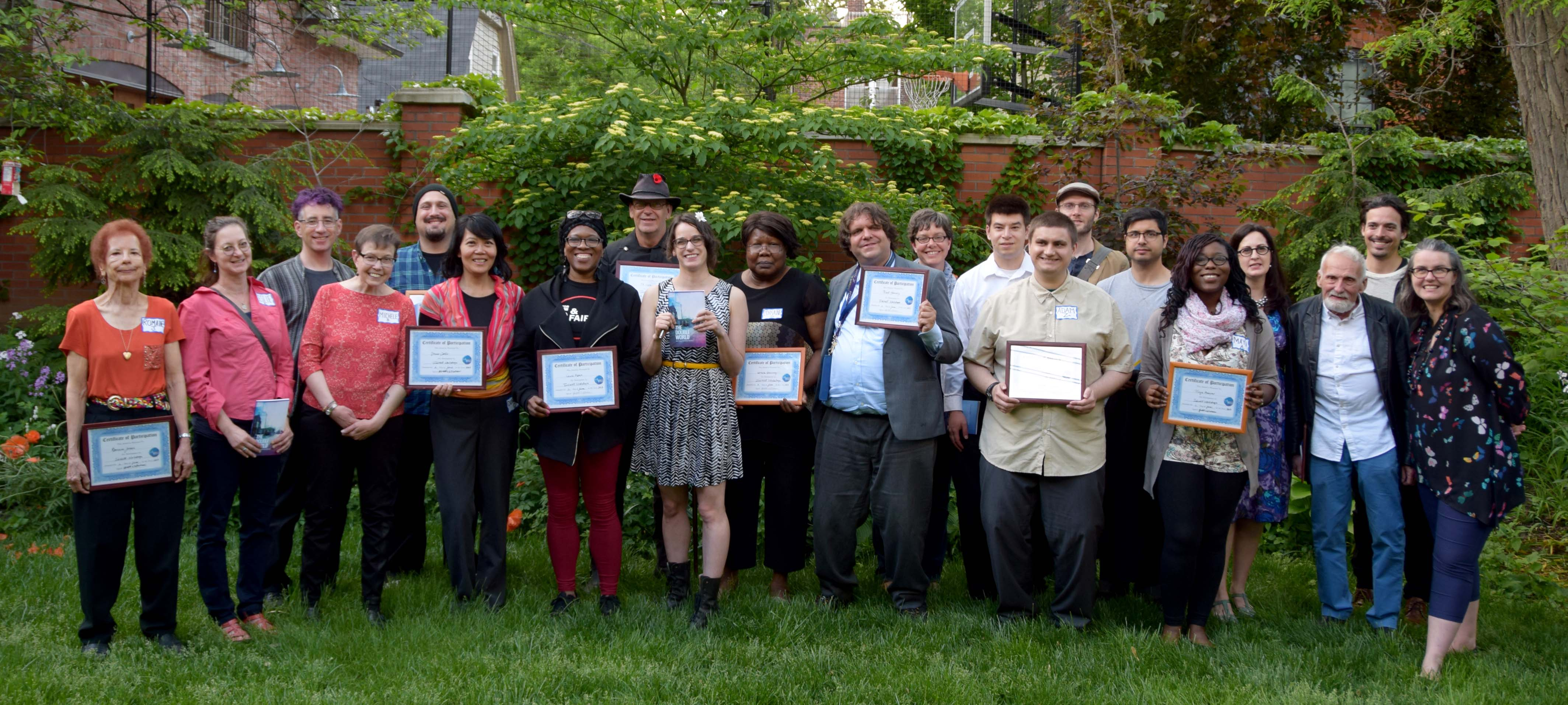 InkWell participants, instructors, and peer support workers stand in a line holding certificates of participation
