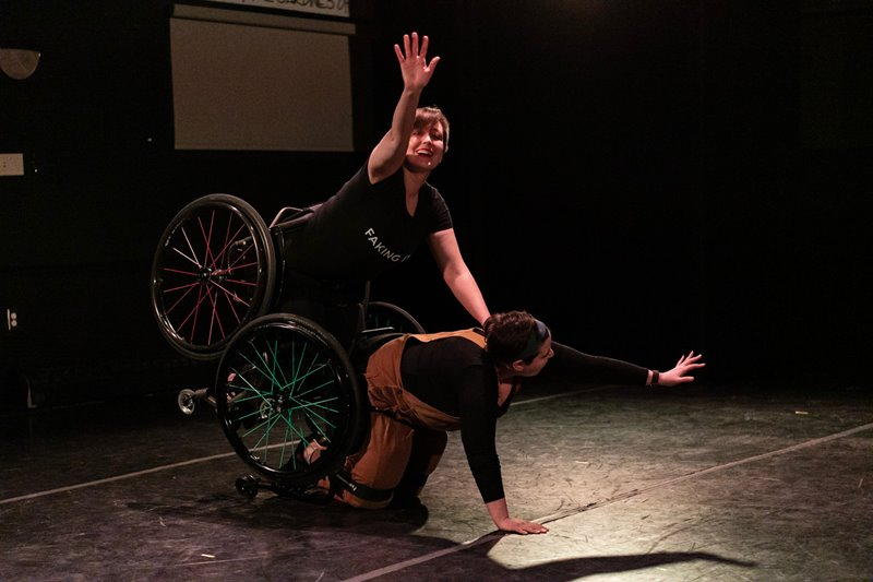 A colour photo of two dancers strapped into wheelchairs. Jen, on hands and knees on Shay's back. Each dancer gazes at their extended arm, smiling