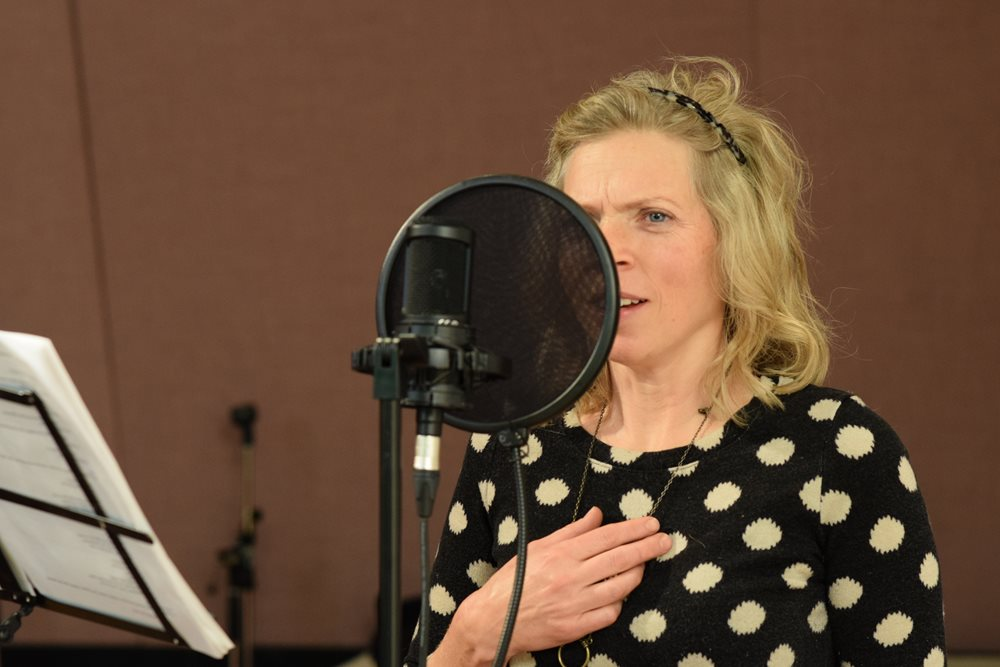 Actor Liisa Repo-Martell speaks into an microphone in a recording booth