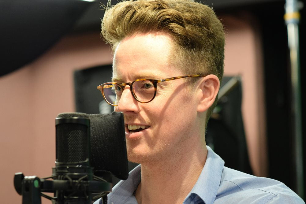 Actor David Patrick Flemming speaks into an microphone in a recording booth
