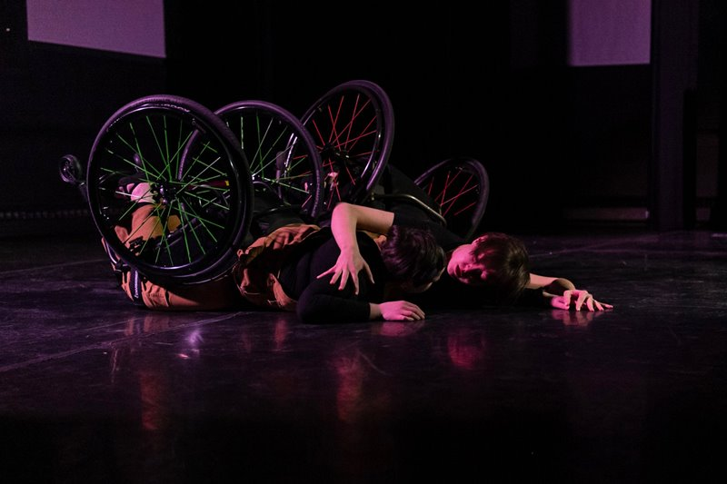 Colour photo of two dancers strapped to wheelchairs, laying face down on the floor. Jen's arm is wrapped around Shay's shoulder as they look intensely at each other.